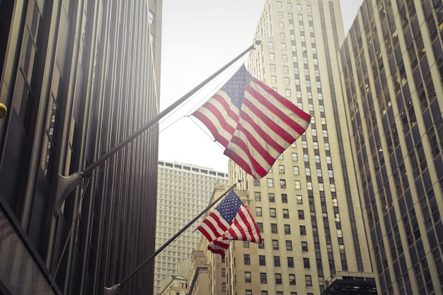 Schuss von zwei amerikanischen oder us-flaggen auf einem hochhaus Kostenlose Fotos