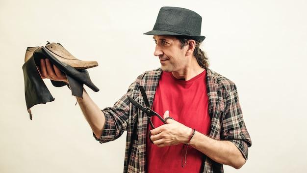 Schuster hält satz werkzeuge und leder. konzept für kleine unternehmen. handgefertigte lederschuhe. schuhmacher, der schuhe in seiner werkstatt modelliert. Premium Fotos