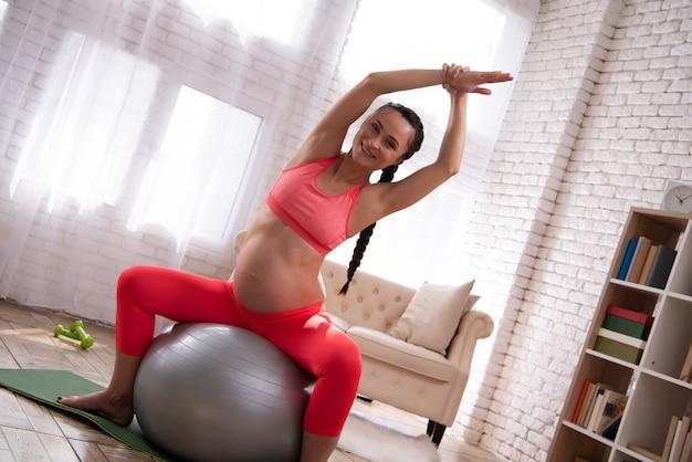 Schwangere frau bildet bauch mit ball aus. Premium Fotos
