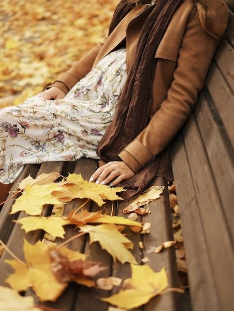 Schwangere frau der junge, die auf einer bank im park sitzt Premium Fotos