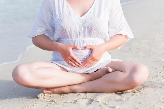 Schwangere frau der junge, die yogaübungen auf dem strand tut Premium Fotos