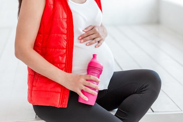Schwangere frau der junge nach eignung whith wasserflasche. sport während der schwangerschaft konzeption Premium Fotos