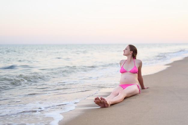Schwangere frau der junge sitzt auf dem seeufer und genießt natur. einsamer strand, zeit vor sonnenuntergang Premium Fotos