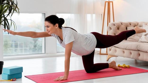 Schwangere frau der seitenansicht, die yoga zu hause tut Kostenlose Fotos