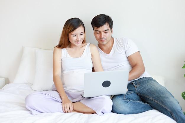 Schwangere frau des asiaten im schlafzimmer, das mit ihrem ehemann sich entspannt Premium Fotos