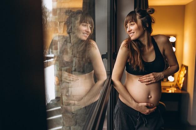Schwangere frau, die am fenster steht Kostenlose Fotos