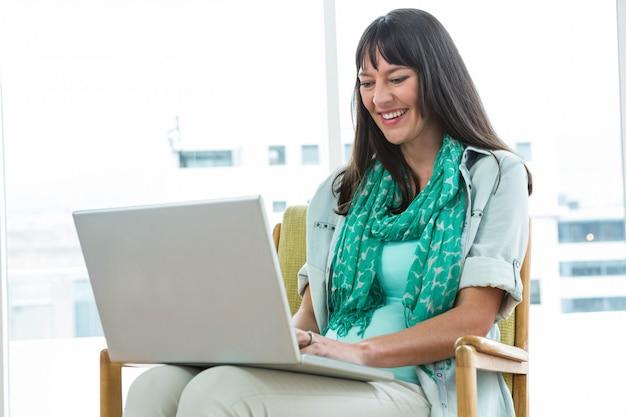 Schwangere frau, die auf stuhl sitzt und zu hause laptop verwendet Premium Fotos