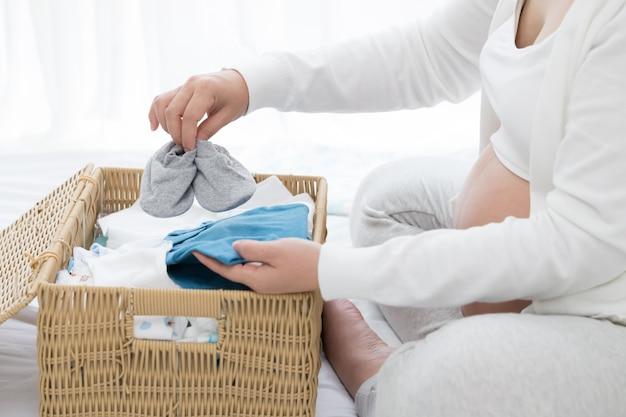 Schwangere frau, die babyprodukte vor pränatal vorbereitet und plant Premium Fotos