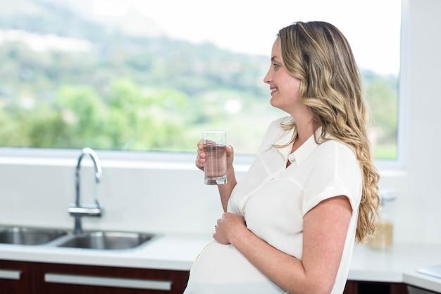 Schwangere frau, die ein glas wasser in der küche trinkt Premium Fotos