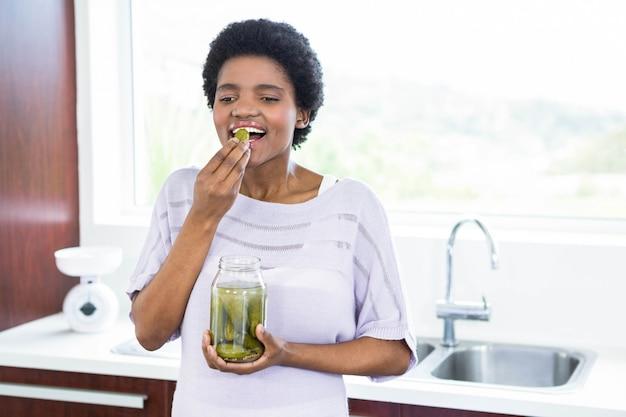 Schwangere frau, die essiggurken in der küche isst Premium Fotos