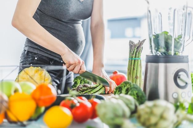 Schwangere frau, die gesundes lebensmittel kocht Kostenlose Fotos