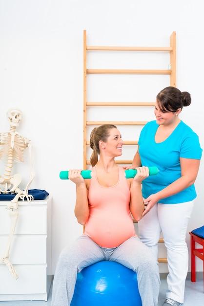 Schwangere frau, die mit dummköpfen in der physiotherapie ausarbeitet Premium Fotos