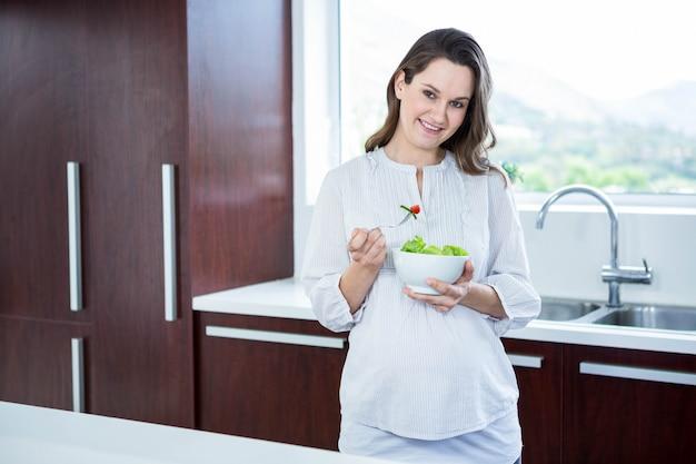 Schwangere frau, die salat in der küche isst Premium Fotos