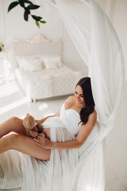 Schwangere frau im weißen kleid, das auf bett liegt und