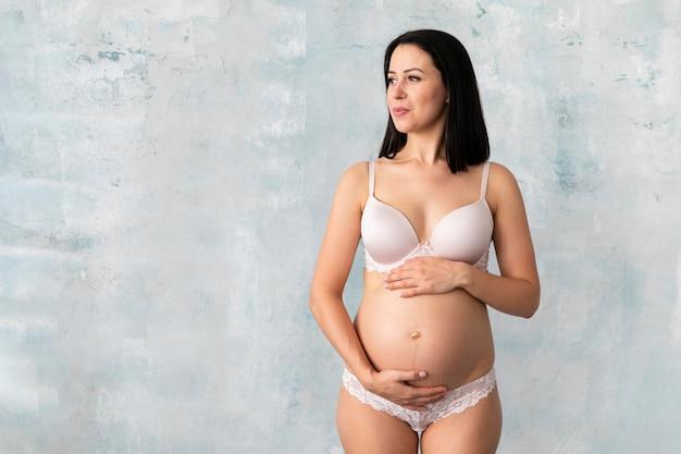 Schwangere frau in der unterwäsche mit exemplarplatz Kostenlose Fotos
