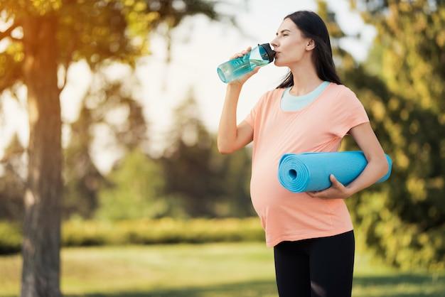 Schwangere frau in einem rosa t-shirt steht im park. Premium Fotos