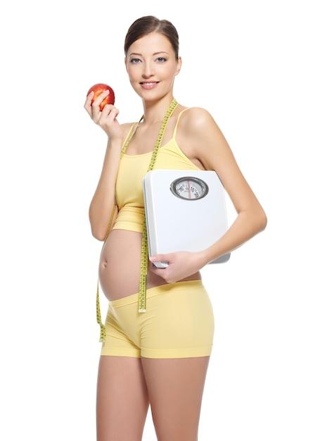 Schwangere frau in gelber sportlicher kleidung, die roten apfel und gewichtswaage auf weiß hält Kostenlose Fotos
