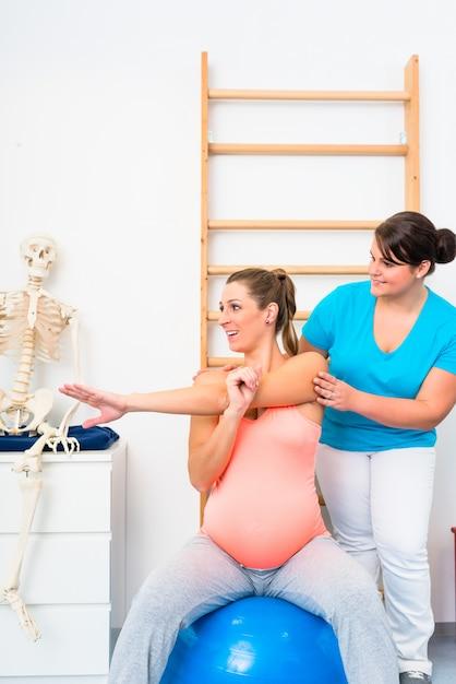 Schwangere frau macht übungen mit physiotherapeuten Premium Fotos