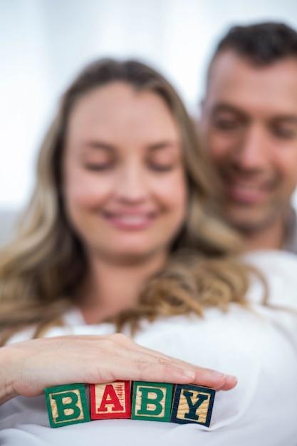 Schwangere frau mit babywürfeln auf ihrem bauch und von ihrem ehemann, der zu hause auf einem sofa liegt Premium Fotos