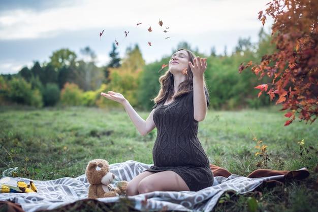 Schwangere frau mit bauch sitzt auf einer decke und wirft gelbe blätter Premium Fotos