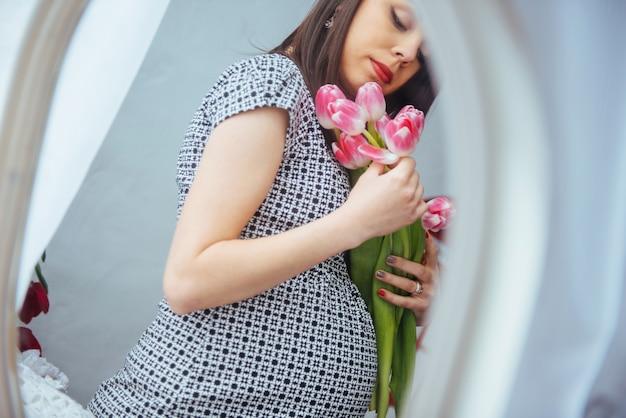 Schwangere frau mit blumen Premium Fotos
