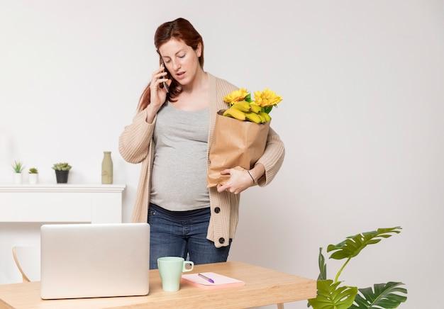 Schwangere frau mit blumenstrauß, der über telefon spricht Kostenlose Fotos
