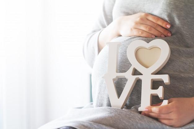 """Schwangere Frau mit dem Wort """"Liebe"""" Kostenlose Fotos"""