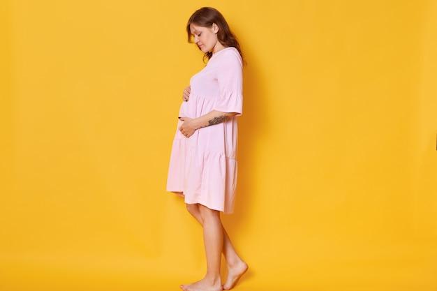 Schwangere frau mit ertrunkenem haar, im rosa puderkleid, umarmenden bauch. elegante und stilvolle frau posiert barfuß, schaut auf ihren bauch. konzept von pragnancy und mutterschaft Kostenlose Fotos