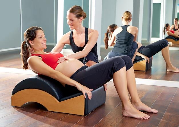 Schwangere frau pilates übung rollen zurück Premium Fotos