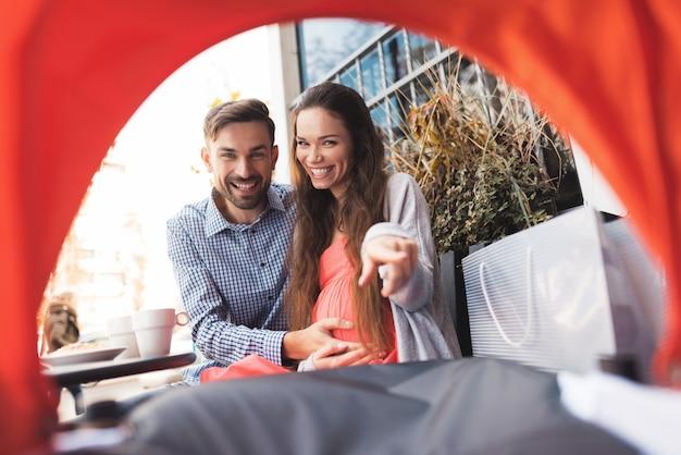 Schwangere frau und ein mann schauen in den kinderwagen. Premium Fotos