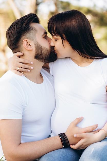 Schwangere frau und ihr geschlagener ehemann, die zusammen auf dem bauch in der natur im freien umarmt Premium Fotos