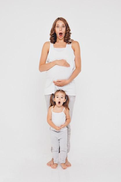 Schwangere frau und kleines mädchen in der sportkleidung auf weißem hintergrund. die mädchen halten ihren bauch. Premium Fotos