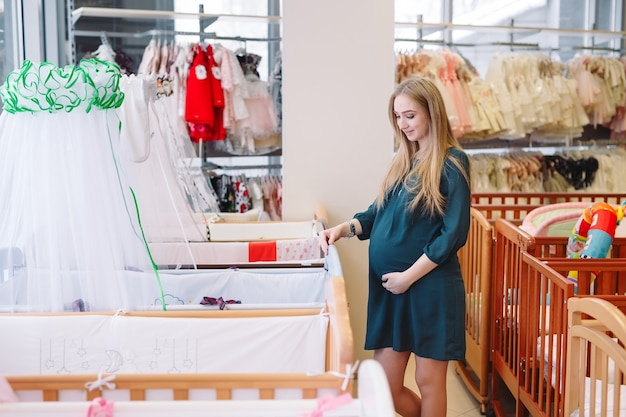 Schwangere frau wählt ein babybett im speicher. Premium Fotos