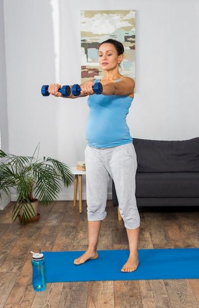 Schwangere frauentraining mit gewichten zu hause auf matte Premium Fotos