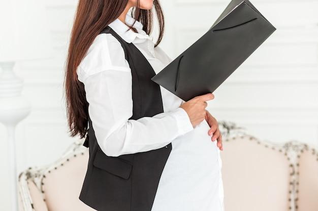 Schwangere geschäftsfrau bei der arbeit in einem büro ein dokument lesend. Premium Fotos