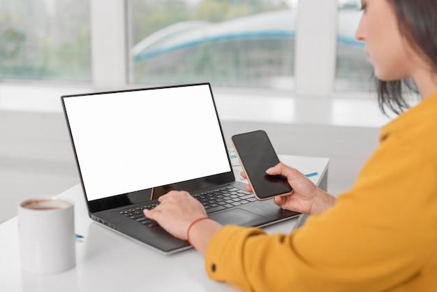 Schwangere geschäftsfrau, die am laptop mit smartphone arbeitet Kostenlose Fotos