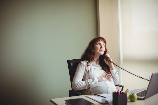 Schwangere geschäftsfrau, die ihren bauch berührt, während sie am telefon spricht Kostenlose Fotos