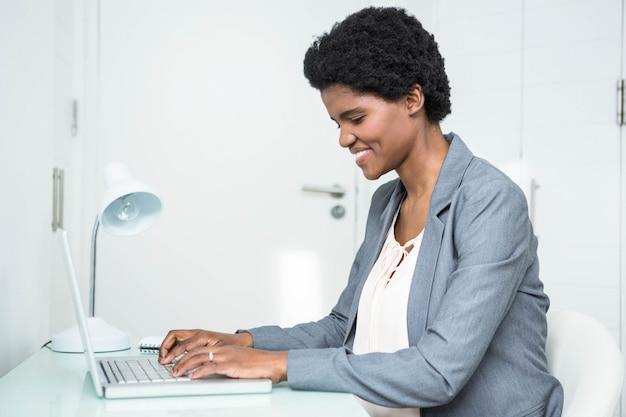 Schwangere geschäftsfrau, die laptop im büro verwendet Premium Fotos