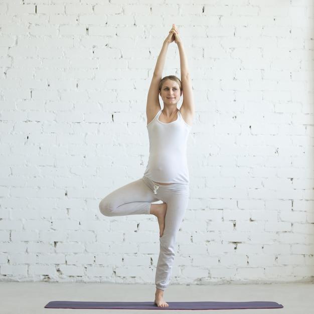 Schwangere junge Frau macht pränatale Yoga. Vrksasana Pose Kostenlose Fotos
