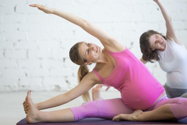 Schwangere junge frauen machen pränatalen yoga. biegen im januar sirsasana pose Kostenlose Fotos
