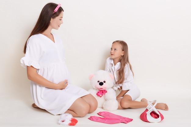 Schwangere junge werdende mutter spielt mit ihrer tochter mit bär Kostenlose Fotos
