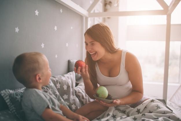 Schwangere mutter und sohn des kleinen jungen essen einen apfel und einen pfirsich im bett, die morgens zu hause sind. lässiger lebensstil im schlafzimmer. Premium Fotos