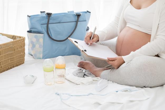 Schwangere vorgeburtliche frauen, die kalender- und checklistengerät für baby, geräte für schwangerschaft vorbereitend planen Premium Fotos