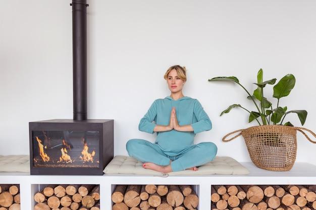 Schwangeres mädchen in der blauen sportkleidung sitzt in lotussitz, der yoga im gemütlichen innenraum tut Premium Fotos