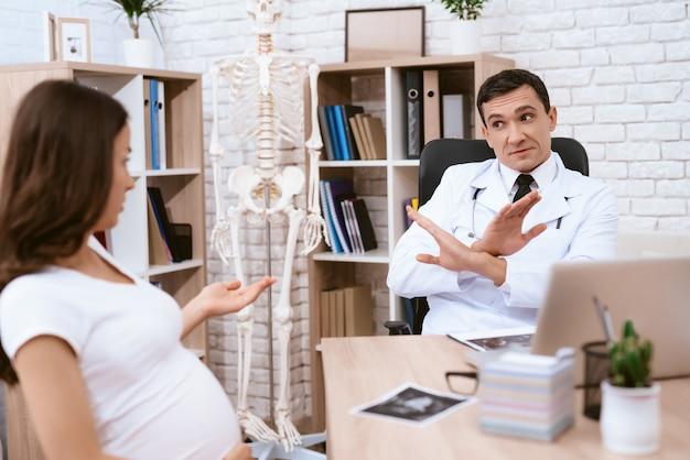Schwangeres mädchen und doktor sprechen ernsthaft in der arztpraxis. Premium Fotos