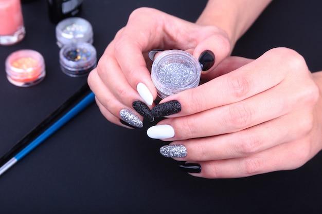 Schwarz-weiße nail art maniküre. feiertagsart helle maniküre mit scheinen. Premium Fotos