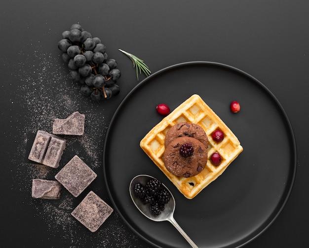 Schwarzblech mit waffeln auf einem dunklen hintergrund mit schokolade und trauben Kostenlose Fotos