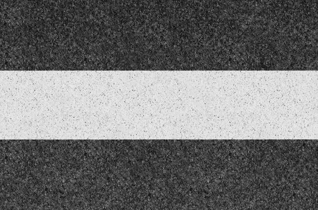 Schwarze asphalthintergrundbeschaffenheit mit gelber linie Premium Fotos