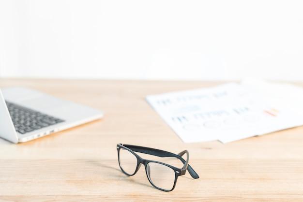 Schwarze brillen vor laptop und diagramm auf hölzernem schreibtisch Kostenlose Fotos