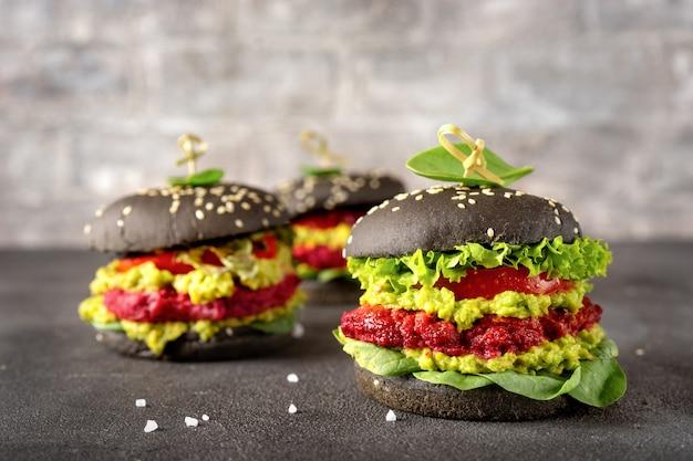 Schwarze burger des strengen vegetariers mit pastetchen der roten rübe auf dunkelheit Premium Fotos